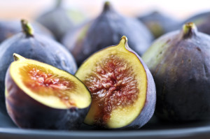 Closeup view of figs sliced in half on a blue plate