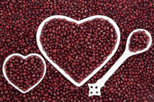 Adzuki bean health food in heart shaped porcelain dishes and spoon forming an abstract background.