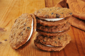 A stack of cream filled oatmeal molasses sandwich cookies