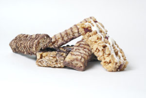 Studio shoot of five granola bars. Four chocolate granola bars and one with white chocolate and raspberry.