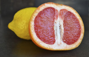A grapefruit and a lemon are on dark brown background.