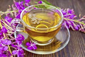 Herbal tea in a glass cup and fresh flowers fireweed against the backdrop of wooden planks