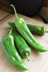 Four fresh bright green chiles from the American Southwest, on a wooden cutting board. Sitting on a tiled kitchen counter with a black tortilla skillet in the background. These fall into the green chile categories of New Mexico green chile, Anaheim chile, Sandia and Hatch green chiles, to name a few. Fresh green chiles on a cutting board imply that they are ready to be roasted and prepared for green chile sauce, stuffed chiles, or any number of green chile recipes. Green chiles are associated with Southwest cuisine, more notably New Mexican cuisine.