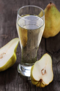 Pear cider and pears on rustic wooden table