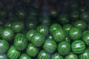 Close up of green candy gum balls in candy machine